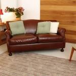 O sofá não precisa ficar encostado na parede. Nesta foto, o modelo de dois lugares, de couro, acabou enviesado em um canto
