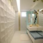 Neste banheiro foram utilizadas placas cimentícias que curam sem o auxílio de fornos. Elas acompanham uma tendência muito forte de volumes e superfície tridimensionais. O resultado sugere sensação de movimento.